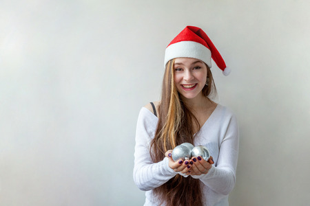 Girl in Santa hat with christmas balls in the hands