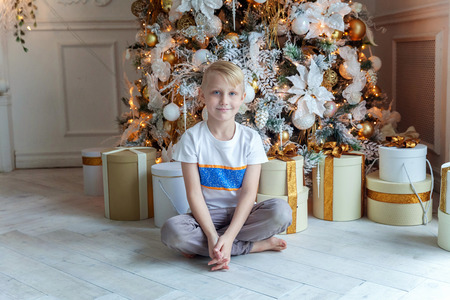Young boy opens a gift under a Christmas tree