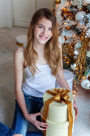 Young girl opens a gift under a Christmas tree