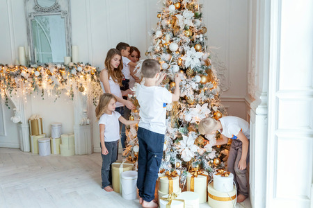 mother and five children decorating a Christmas tree