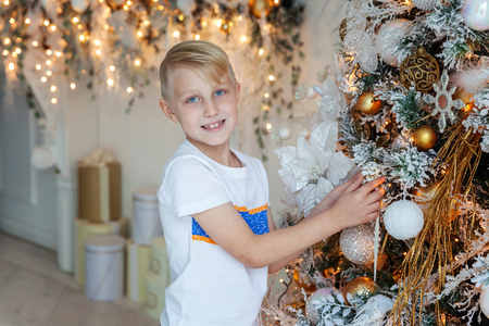Young boy decorating Christmas tree Stock Photo