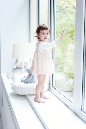 Baby girl smiles in a room near the window Stok Fotoğraf