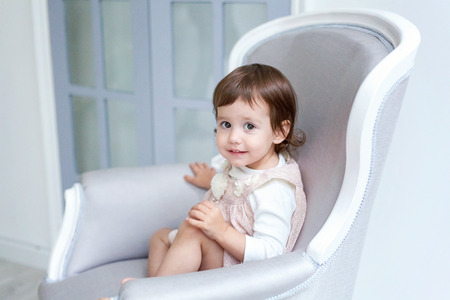 Sweet little girl at home sitting on modern chair relaxing in white living room Stock Photo