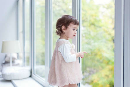 Cute smiling baby girl standing at home near window