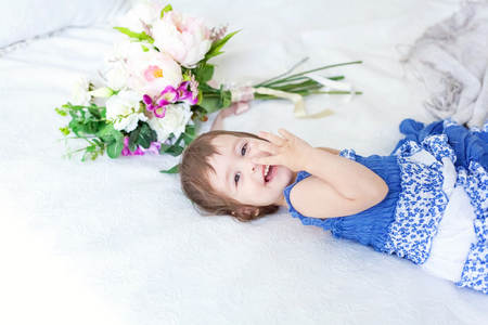 Funny and cute brunette little smiling girl playing on bed in bedroom. White interior with big bed