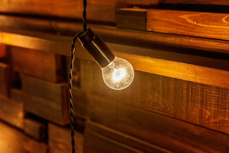 Hanging light bulb over the wooden background, mockup poster. Background wood planks with lamps Stock Photo