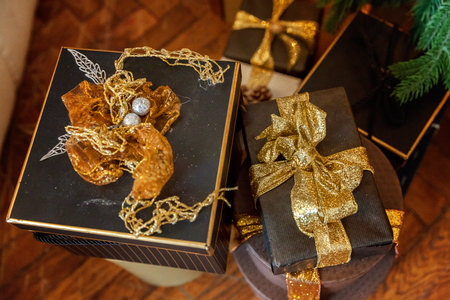 Black paper gift boxes with golden ribbon bow near the Christmas tree. Classic christmas and New Year decorated interior room with presents and New year tree.