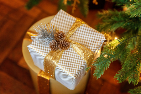White and gold paper gift boxes with golden ribbon bow near the Christmas tree. Classic christmas and New Year decorated interior room with presents and New year tree.