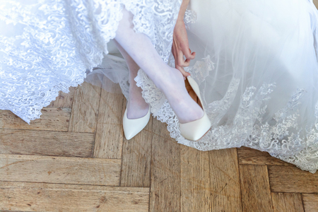 The bride wears white shoes on foot in the wedding day. close-up shoot