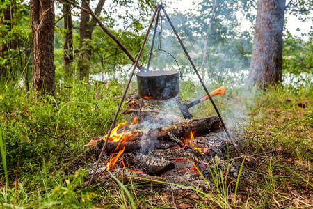 Cast iron pot cooks over open fire in a campsite