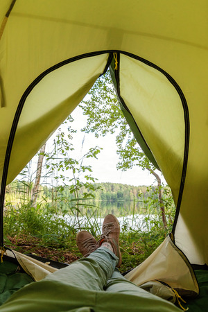 Photo of a woman legs in green jeans and sneakers laying in tourist tent with a view of the forest and lake in sunny summer day. Stock Photo