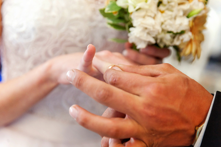 marriage hands with rings. grooms hand putting a wedding ring on the brides finger Stock Photo