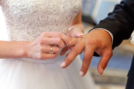 marriage hands with rings. birde wears the ring on the finger of the groom
