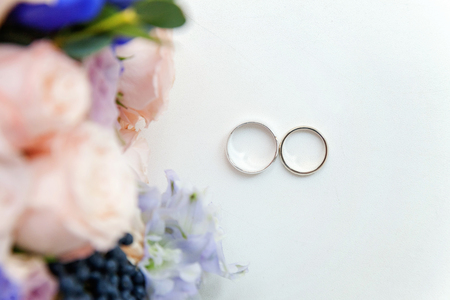 Beautiful wedding rings lie on a table against the background of a bouquet of flowers