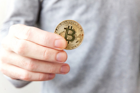 Cryptocurrency golden bitcoin coin in man hand. Electronic virtual money for web banking and international network payment. Symbol of crypto currency Stock Photo