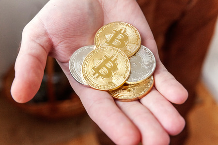 Cryptocurrency golden and silver bitcoins coin in man hand. Electronic virtual money for web banking and international network payment. Symbol of crypto currency Stock Photo