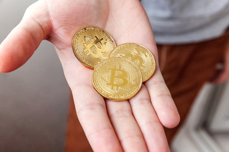 Cryptocurrency golden bitcoins coin in man hand. Electronic virtual money for web banking and international network payment. Symbol of crypto currency