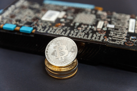 Bitcoins lie on the video card, concept of mining. Electronic virtual money for web banking and international network payment. Symbol of crypto currency Stock Photo