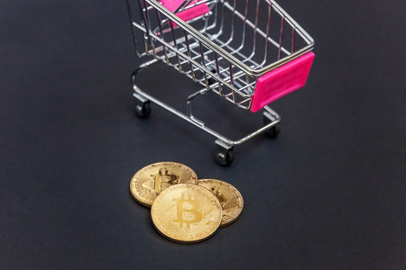 Stack of coins bitcoin in mini shopping cart toy, concept of mining. Electronic virtual money for web banking and international network payment. Symbol of crypto currency