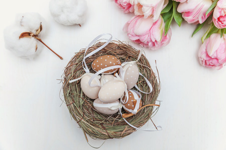 Spring greeting card. Easter eggs in the nest with cotton and tulips on rustic wooden planks. Easter concept. Flat lay. Spring flowers tulips