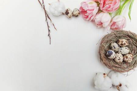 Spring greeting card. Easter eggs in the nest with cotton, willow branch and tulips on white wooden background. Easter concept. Flat lay. Spring flowers tulips