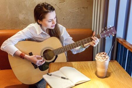 Young smiling hipster woman sitting playing guitar and write a song at cafe. Girl learning to play music