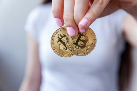 Cryptocurrency golden bitcoin coin in woman hand. Electronic virtual money for web banking and international network payment. Symbol of crypto currency Stock Photo