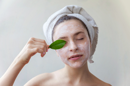 Beauty portrait of a smiling brunette woman in a towel on the head with white nourishing mask or creme on face and green leaf in hand on white background isolated. Skincare cleansing eco organic cosmetic spa relax concept Stok Fotoğraf