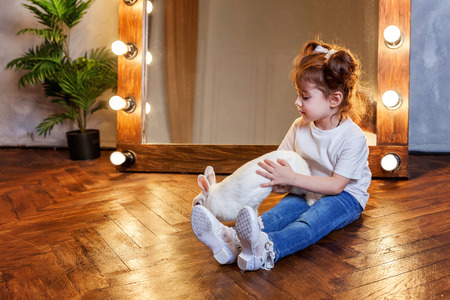 Easter celebration, pet care and animals concept. Cute happy little girl sitting on the floor and playing with adorable white rabbit bunny in modern room over mirror