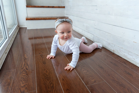 Little smiling baby girl one year old crawl on the floor in bright room near window and laughs. Happy kid playing at home