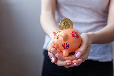 Piggy bank, woman hand holds golden bitcoin coin virtual money. Cryptocurrency and saving concept