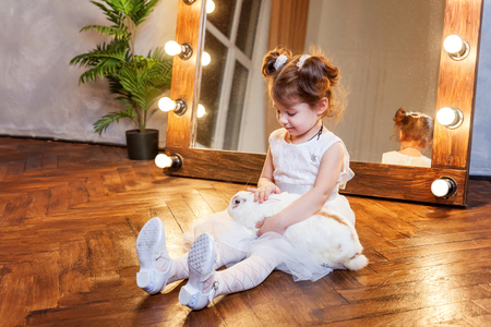Easter celebration, pet care and animals concept. Cute happy little girl sitting on floor, holding and playing with adorable white fluffy rabbit bunny in modern room over mirror