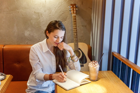 Young smiling hipster woman sitting playing guitar and write a song at cafe. Girl learning to play music Banco de Imagens