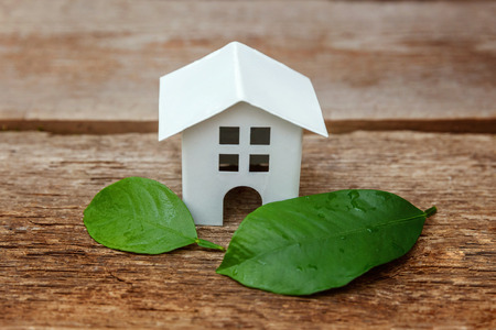 Miniature white toy model house with green leaves on wooden backgdrop. Eco Village, abstract environmental background.