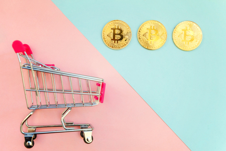 Stack of coins bitcoin in mini shopping cart toy on pastel color background, concept of mining.