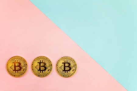 Gold bitcoin on on pink and blue pastel geometric background. Electronic virtual money for web banking and international network payment. Symbol of crypto currency Stock Photo