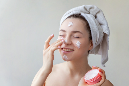 Beauty portrait of a smiling brunette woman in a towel on the head applying white nourishing mask or creme on face on white background isolated. Skincare cleansing spa relax concept