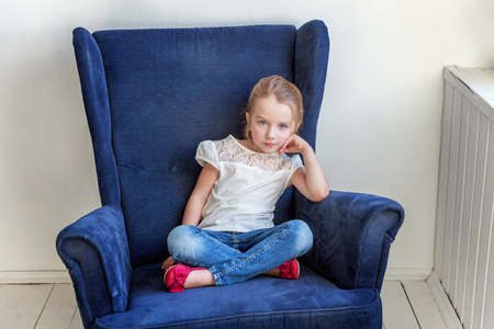 Sweet little girl in jeans and white T-shirt at home sitting on modern cozy blue chair relaxing in white living room. Childhood, schoolchildren, youth, relax concept
