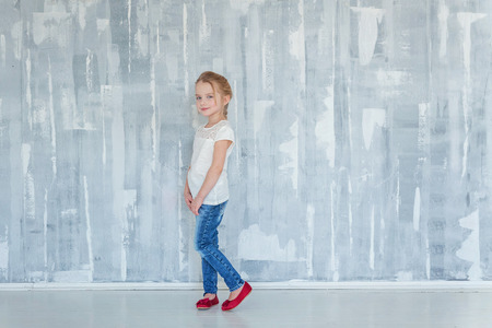 Sweet happy little girl in blank white t-shirt standing against grey textured wall background