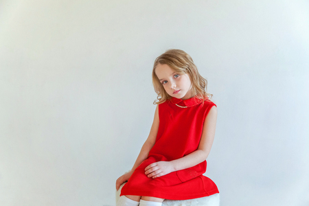 Sweet happy little girl in red dress sitting on chair against white wall background in bright room 스톡 콘텐츠