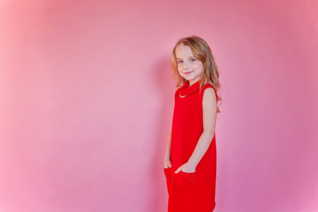 Little cute sweet smiling girl in red dress standing on pink colourful pastel trendy modern fashion pin-up background