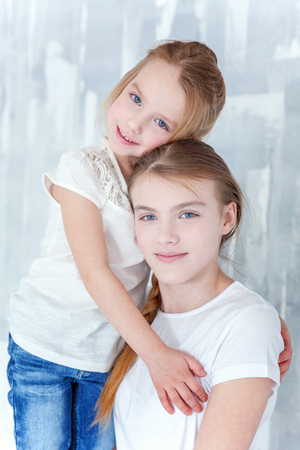 Two happy kids standing against grey textured wall background and embracing. Adorable pretty little girl hugging tight cute teenage girl, showing her love and care. Sisters having fun at home