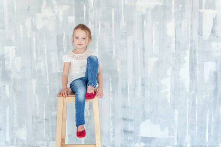 Sweet happy little girl in blank white t-shirt sitting on chair against grey textured wall background