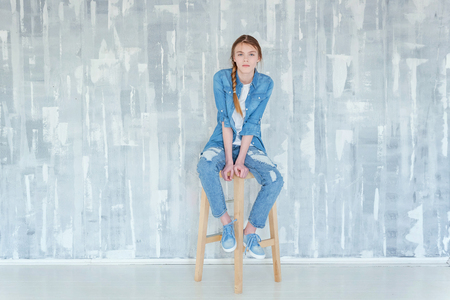 Young happy cute teenage girl in jeans, denim jacket and white T-shirt sitting on chair against grey textured wall background. Casual daily lifestyle. Schoolgirl student education and school concept Stock fotó