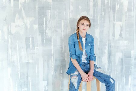 Young happy cute teenage girl in jeans, denim jacket and white T-shirt sitting on chair against grey textured wall background. Casual daily lifestyle. Schoolgirl student education and school concept Фото со стока
