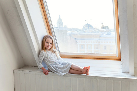 Little cute sweet smiling girl in white dress sitting on the window sill in bright light living room at home and thinking