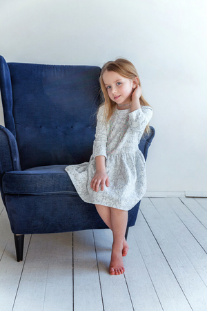 Sweet little girl in grey dress at home sitting on modern cozy blue chair relaxing in white living room