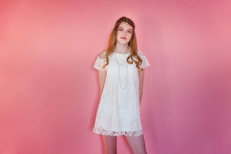 Happy teenage girl smiling. Closeup portrait young happy positive woman wearing white dress standing on pink colourful pastel trendy modern fashion pin-up background. European woman. Positive human emotion facial expression body language