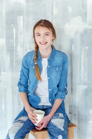 Young happy cute teenage girl in jeans, denim jacket and white T-shirt sitting on chair against grey textured wall background, holding paper cup and drinking coffee. Casual daily lifestyle