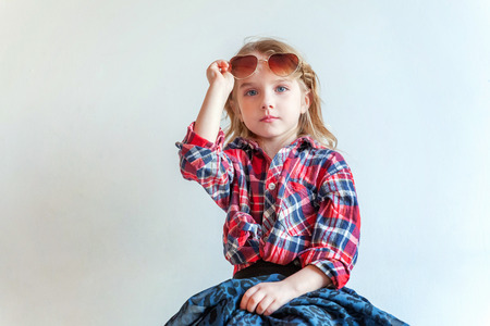 Sweet happy adorable fashion young little girl dressed like hipster hippie gipsy cowboy in sunglasses sitting on modern chair posing in white wall background in light bright room. Lifestyle people tre
